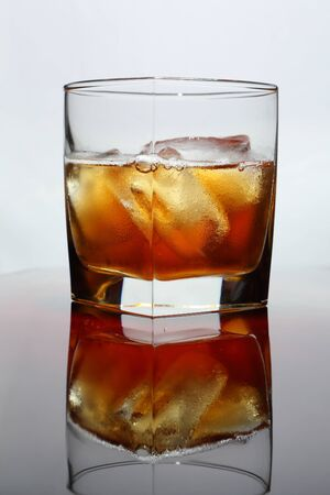 A glass of whiskey with ice on a glossy table and a light background