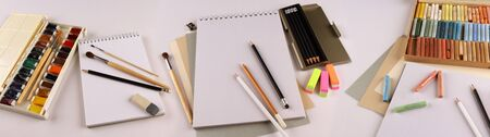 Pastels, watercolors, pencils, eraser and drawing pads on a white glossy table