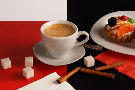 Still life with a white Cup of coffee, cinnamon and cakes on a red-black-and-white background