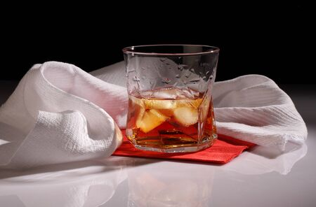 A glass of whiskey with ice on a glossy table against a white towel