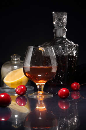 Glass of cognac, cherry berries, lemon and decanter on a glossy table and dark background
