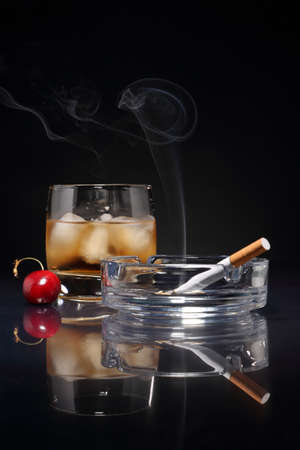 Whiskey on the rocks and an ashtray with a cigarette on a dark background