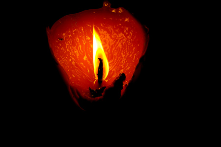 closeup of burning candle isolated on black dark background one flame at night macro brightly