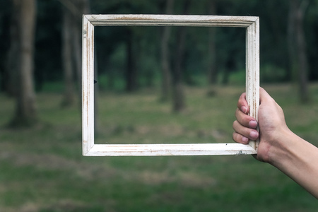 man hold shabby chic style white vintage wooden frame blur green nature concept idea background