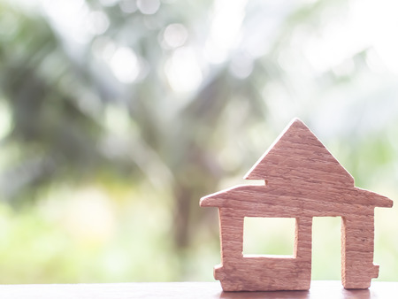 Wooden house  on a green blur bokeh background. Love nest, relationships. Buying a house . Affordable housing. concept idea background