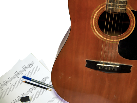 acoustic guitar with bronze string is used composing note song  on the paper have pen pencil ruber isolated white background Stock Photo