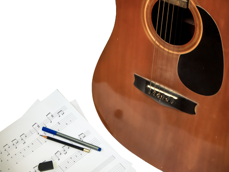 acoustic guitar with bronze string is used composing note song  on the paper have pen pencil ruber isolated white background Imagens