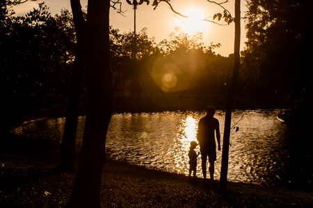 Father and son playing in the park near lake at the sunset time.  Concept of family love and of summer vacation silhouette photography