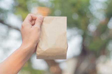Close up female holds in hand brown clear empty blank craft paper bag for take away on blur bokeh nature background. Packaging bag.