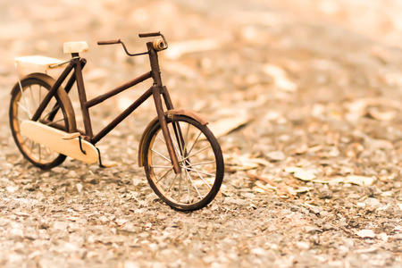 Retro styled image of a nineteenth century bicycle wooden model on a nature background