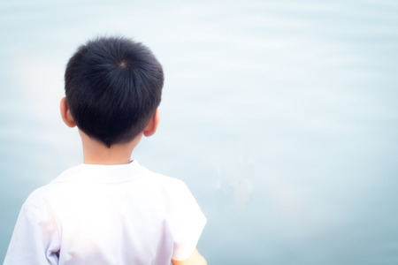 daydream. child dreaming sitting on a  pier near the water and looking into the lake imagination hopeful future concept idea of new generation background