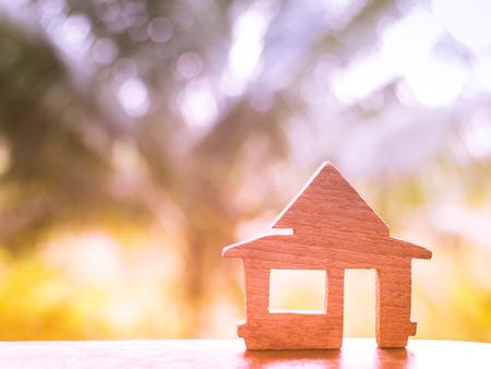 Wooden home model put on the desk, Loan for real estate or for buy a new house concept, blur nature background Reklamní fotografie