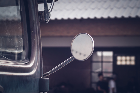 close-up of a driving mirror on a vintage vehicle.old warehouse blur background