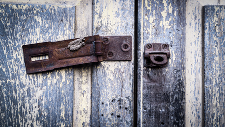 Vintage rustic stain old lock stain U line Hasp Hardened Staple equipment on painted wooden door. Old lock on the door, lock on the door of an old farmhouse, true village style, close-up, focus on lock.