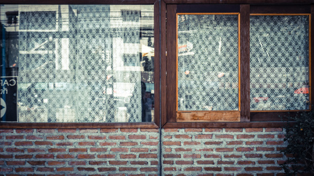 Old brick wall with brick and lovely window. white lattice curtain.