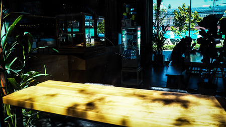wooden table in front of the blur background with the shadow of tree flower and window, coffee shop, lifestyle.
