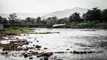 Long bridge across small lake river in the mountain forest in summer. Beautiful scenetic landscape