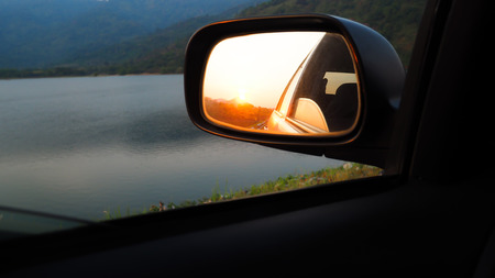 Orange landscape sunset reflect in mirror of car. Rear View Mirror Reflection on sun set. Road trip concept idea