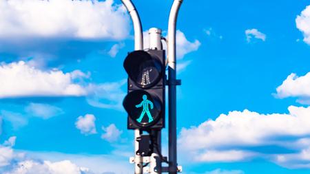 Green traffic light signal for pedestrians on the crosswalk against blue sky in summer. Travel. Moving forward concept idea. Reklamní fotografie
