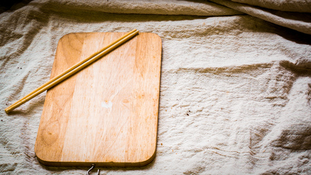 Wooden plate blank with chopsticks, on natural linen cover table on white table, top view .cooking food menu idea background