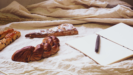 Breads and toast for breakfast and note book on white bed sheet background, Healthy breakfast. Morning health lifestyle concept idea background Reklamní fotografie