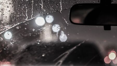 Interior of car when rains. Defocused blur of light on the road in a raining day Stock Photo