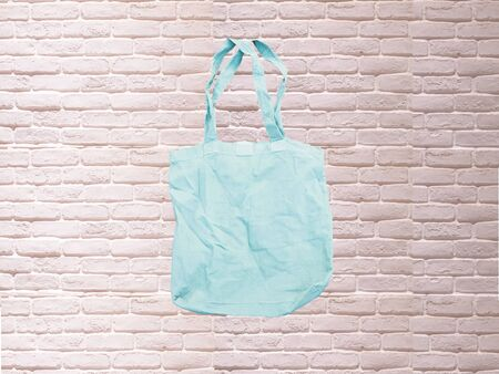 Mock up Tote bag eco hipster white cotton fabric Shopping bag in blue . white brick eall rustic background Stock fotó