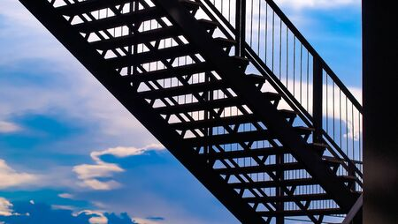 side view of outside metal staircase or fire exit stair with sheet  against blue sky. moving up concept idea Stock Photo