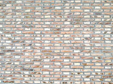 Orange Random Brick Glass & Resin Mesh Mounted Mosaic Tiles creates a beautiful multi-dimensional effect. Old-fashioned brick building. Background of random orange green tone brick wall, pattern, close
