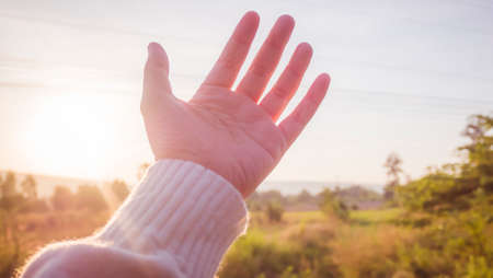 soft focus Woman hand reaching towards nature and sky