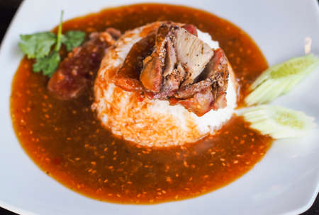 Red barbecued pork on rice, food serve with sweet curry and vegetable (cucumber, coriander) on white ceramic plate.