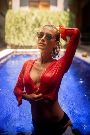 foto di moda di bella donna con capelli castani in camicetta rossa trasparente e occhiali a specchio in posa in piscina blu a Bali