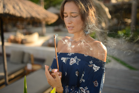fashion photo of beautiful woman with short brunette hair posing with close eyes and smoke incense on asian background in Bali Archivio Fotografico