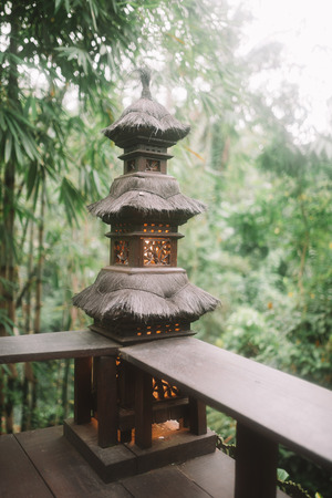 Beautiful photo of black asian street light at the wood veranda on tropical forest background in Bali