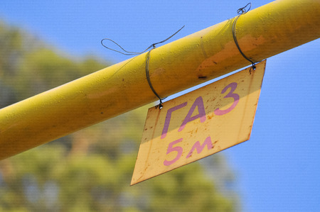 Photo of a yellow gas pipe with a sign Gas on background of blue sky Stock Photo