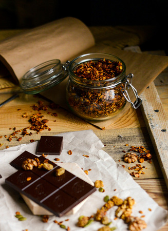 beautiful food photo of tasty dark chocolate with homemade granola on the rustic background wood table