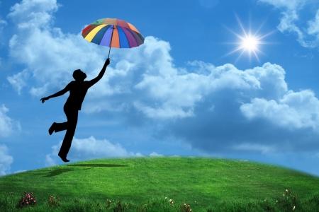 Mann springt mit Regenschirm Standard-Bild