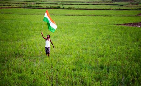 boy with indian national flag on agricultural land Editorial