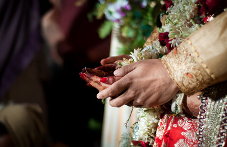 hand holding flower: Indian wedding rituals Stock Photo