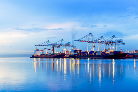 unloading: Container Cargo port freight ship with working crane bridge in shipyard at dusk for Logistic Import Export background, Containers loading by crane in the evening , Trade Port , Shipping Stock Photo
