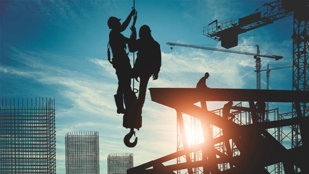 silhouette of construction workers working in high places with crane hoist wire sling welding truss of constructure Фото со стока