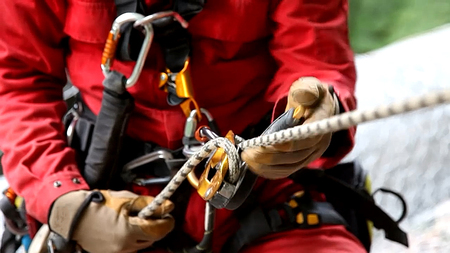 abseiling on a buining with harness rope helmet blurred
