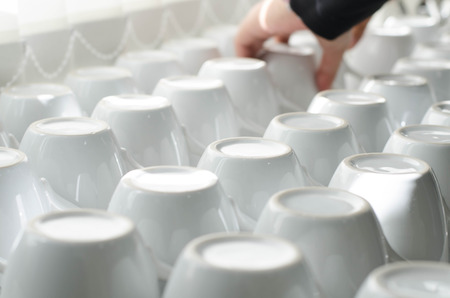 neatly stacked: Abstract background coffee cups neatly stacked in rows  of one another with the handles in each alternating row facing the opposite direction