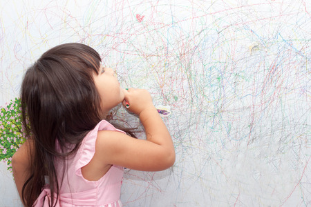 girl drawing with crayons on the wallpaper