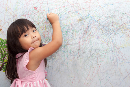 family with one child: girl drawing with crayons on the wallpaper