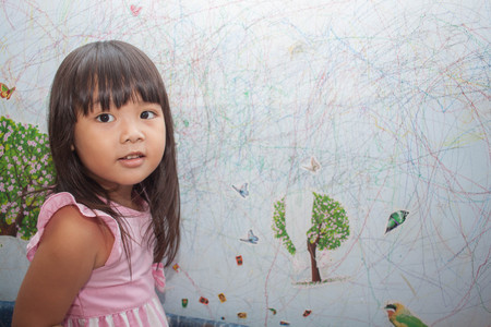 kid drawing: girl drawing with crayons on the wallpaper