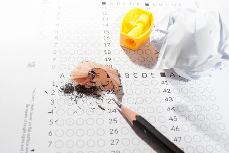 eraser mark: black Pencils lying on a computerized exam answer sheet.