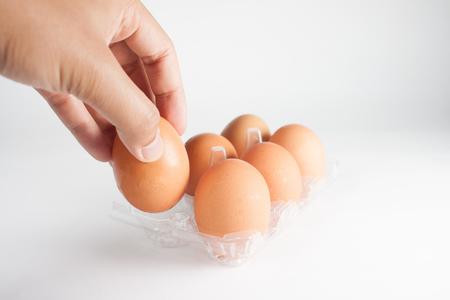 egg box: Men Hand selected Egg in egg box plastic on white background.