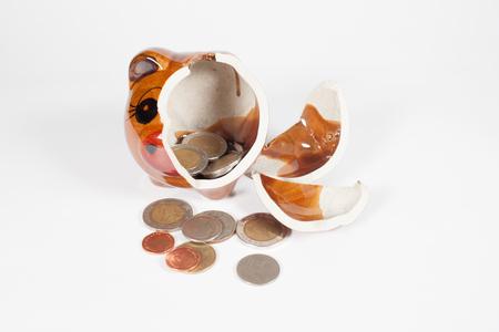 side shot: Piggy bank broken with money inside on white background.