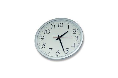 Round metal clock on white wall.